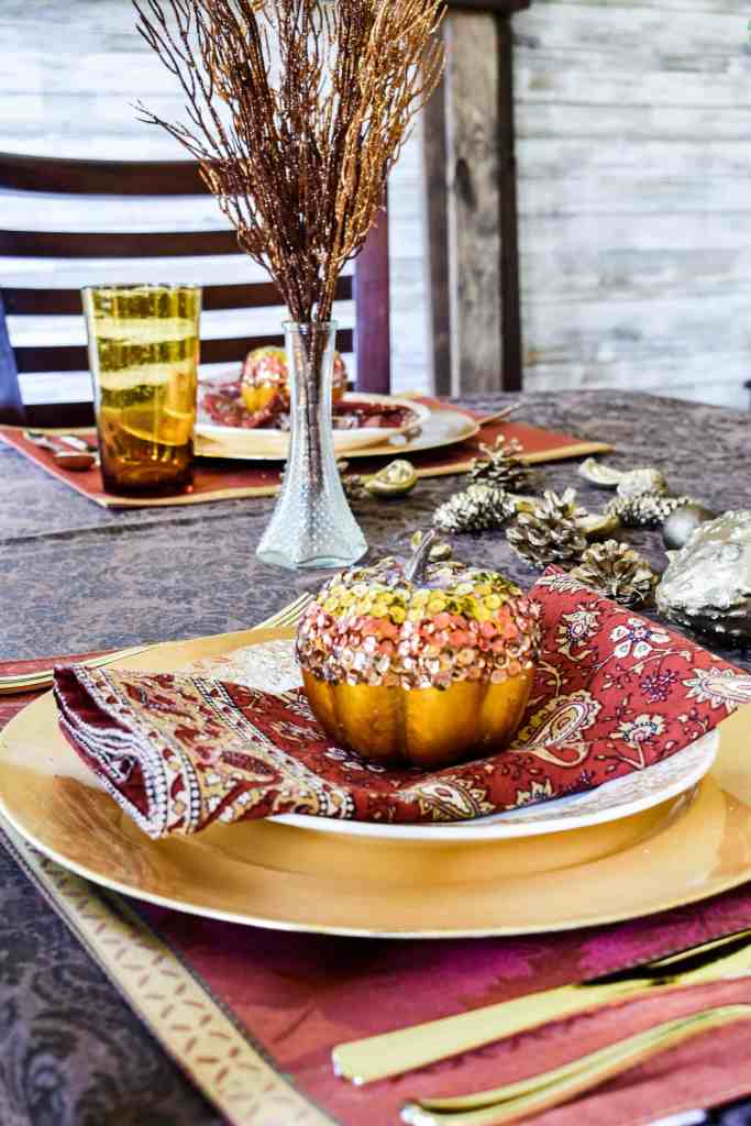 glam pumpkin covered with sequins on top of place setting on a  fall tablescape.