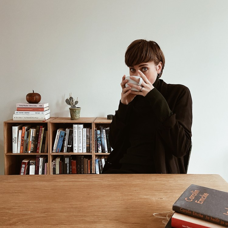 Portrait of Camilla Zuleger, drinking a cup of coffee in front of bookcase