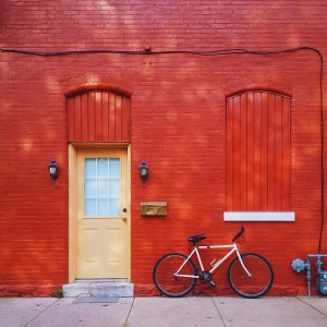 Red Brick building with yellow door and a bicycle under the window