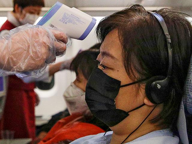 Stewardesses take temperatures of passengers as a preventive measure for the coronavirus on an Air China flight from Melbourne to Beijing (AP photo)
