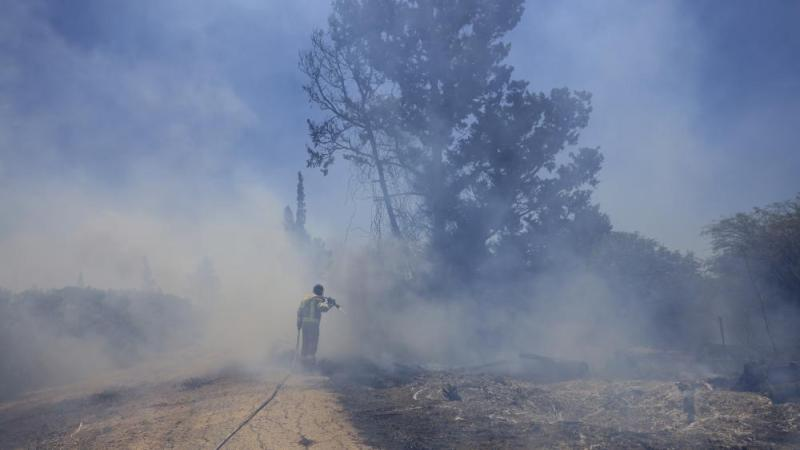 An Israeli firefighter attempts to extinguish a fire caused by an incendiary balloon launched by Palestinians from the Gaza Strip, on the Israel-Gaza border, Israel, Tuesday, June 15, 2021. (AP Photo/Tsafrir Abayov)