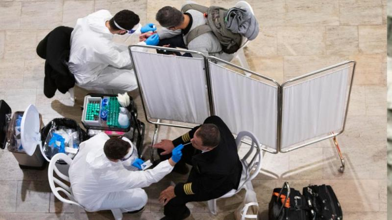 Medical personnel test travelers for COVID-19 as they arrive from abroad at the Ben-Gurion airport near Tel Aviv, Israel, Monday, March 1, 2021. (AP Photo/Sebastian Scheiner)