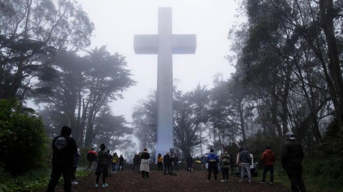 People gather at the Mount Davidson Cross in San Francisco, Sunday, April 12, 2020. Mount Davidson's annual Easter Sunrise Service was canceled for San Francisco's shelter in place orders over coronavirus concerns. (AP Photo/Jeff Chiu)