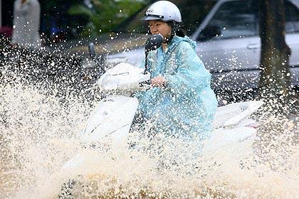 Mulher pilota moto em rua inundada de Hanói; fortes chuvas deixaram ao menos 14 mortos em uma semana no Vietnã (09h11)