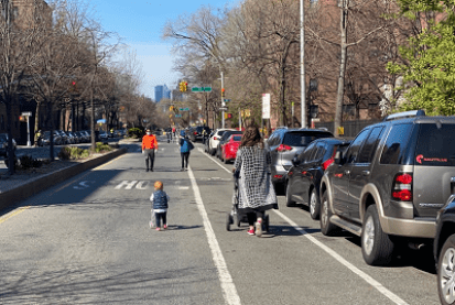 A mother and young child push strollers while walking on a street open to pedestrians and cyclists, while closed to vehicular traffic. Other pedestrians wearing face masks are walking in the distance