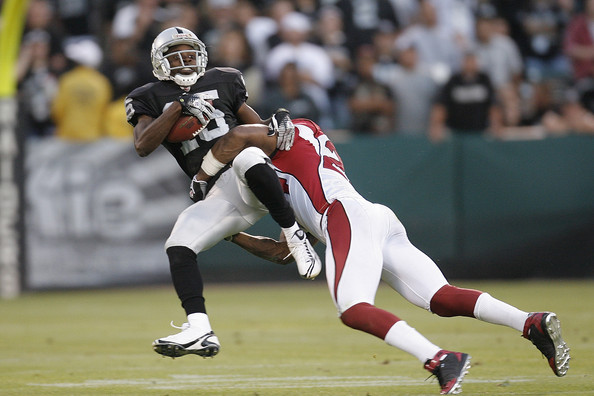Wide receiver Johnnie Lee Higgins #15 of the Oakland Raiders is sent flying by defensive back Adrian Wilson #24 of the Arizons Cardinals during a preseason game on August 23, 2008 at the McAfee Coliseum in Oakland, California.