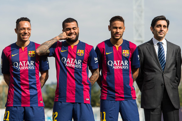 Dani Alves (2ndL) of FC Barcelona jokes as he poses next to his teammates Adriano Correia (L) Neymar and the Telefonica CEO Jose Maria Alvarez Pallete (C) during the presentation of a partnership agreement at Ciudad Deportiva de Sant Joan Despi on February 18, 2015 in Barcelona, Spain.
