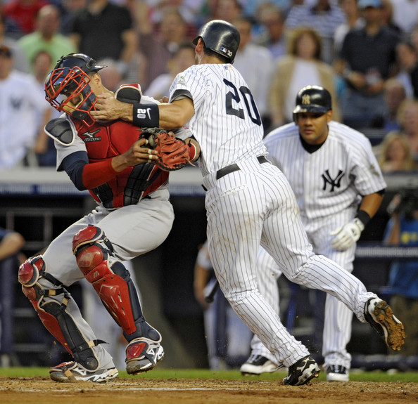 Catcher Victor Martinez #41 of the Boston Red Sox is run into by Jorge Posada #20 of the New York Yankees as he is tagged out at the plate trying to score on a hit by Nick Swisher in the second inning on August 6, 2009 at Yankee Stadium in the Bronx borough of New York City.