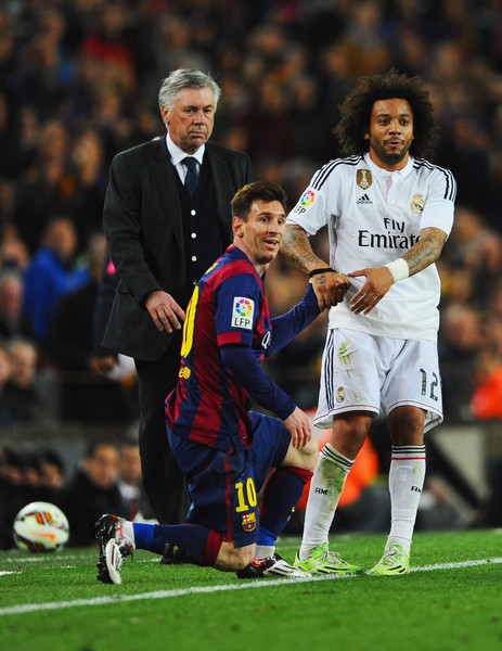 Carlo Ancelotti head coach of Real Madrid CF looks on as Lionel Messi of Barcelona is assisted by Marcelo of Real Madrid CF during the La Liga match between FC Barcelona and Real Madrid CF at Camp Nou on March 22, 2015 in Barcelona, Spain.