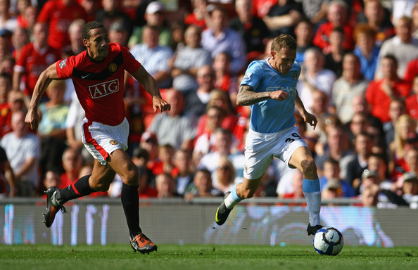Craig Bellamy of Manchester City breaks clear of Rio Ferdinand to score his team's third goal during the Barclays Premier League match between Manchester United and Manchester City at Old Trafford on September 20, 2009 in Manchester, England.