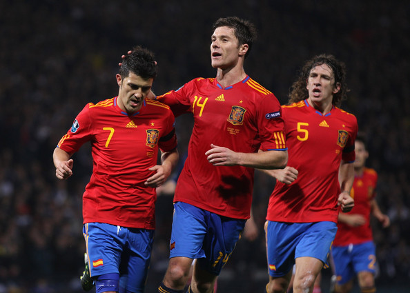David Villa of Spain celebrates with Xabi Alonso after scoring the opening goal from the penalty spot during the UEFA EURO 2012 Group I Qualifier match between Scotland and Spain at Hampden Park on October 12, 2010 in Glasgow, Scotland.