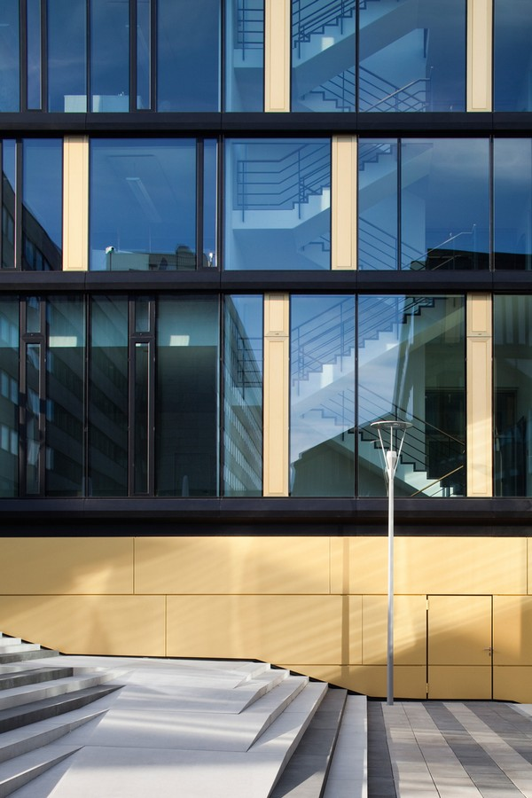 The office facade - Vertical story-high glass panels alternate with room-high window elements with window stops as well as closed goldcolored anodized alu-panels