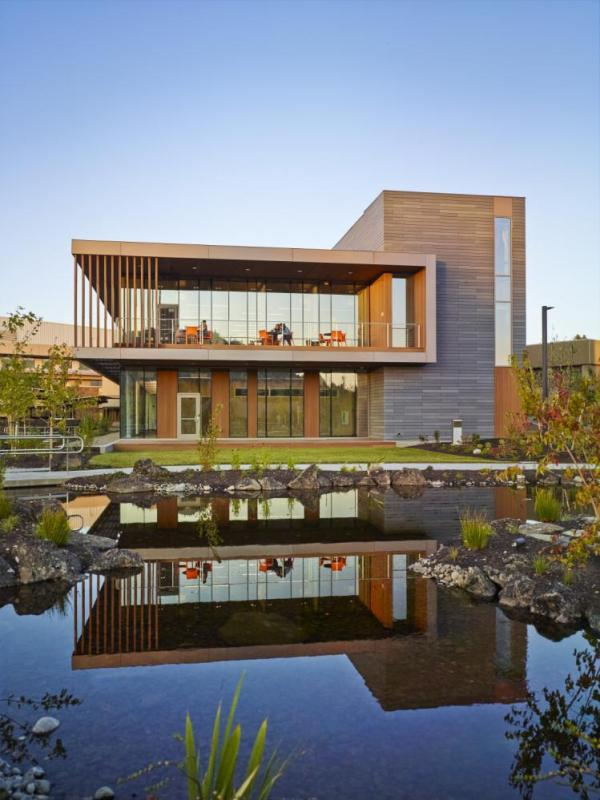 The building's exterior was designed for sustainability, economy and compatibility with a palette of materials complimentary to the natural environment. A new healing garden with a recirculating water feature, was thoughtfully retained from a former irrigation pond, Image Courtesy © Pete Eckert