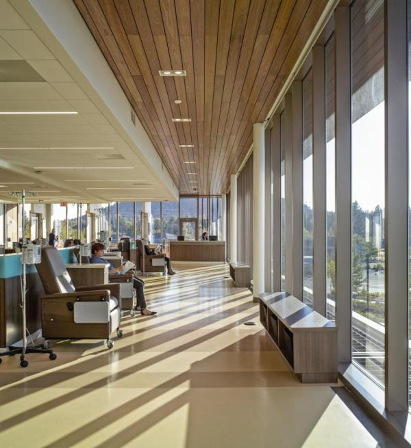 A large, light-filled open plan infusion room, fronted by floor-to-ceiling windows framing the landscape, offers patients a social setting to connect with each other, Image Courtesy © Pete Eckert