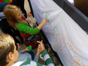 Los niños colorean con sus dedos el logo de AS en San Gerardo.