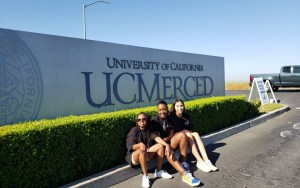 students sitting in front of uc merced sign