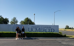 students posing in front of uc merced sign