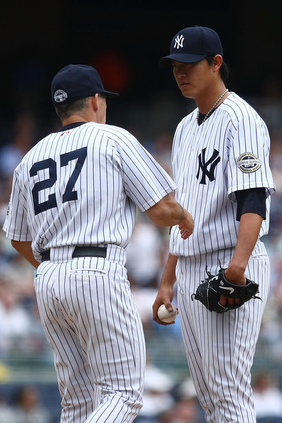 New York Yankees manager Joe Girardi #27 takes pitcher Chien-Ming Wang #40 out of the game in the 5th inning against the Texas Rangers during their game on June 4, 2009 at Yankee Stadium in the Bronx borough of New York City.  (Photo by Chris McGrath/Getty Images) *** Local Caption *** Joe Girardi;Chien-Ming Wang