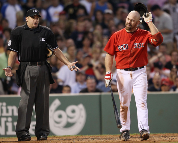 Kevin Youkilis #20 of the Boston Red Sox discusses his strike out with home plate umpire Andy Fletcher in the sixth inning against the Baltimore Orioles on July 2, 2010 at Fenway Park in Boston, Massachusetts.