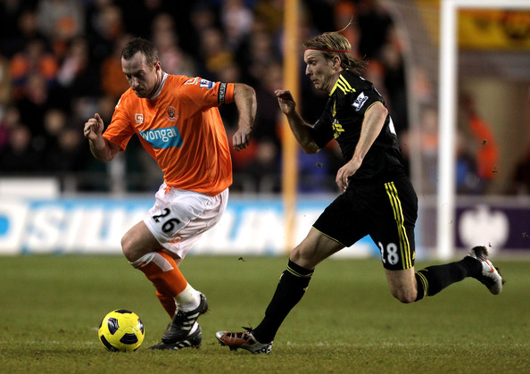 Charlie Adam Charlie Adam of Blackpool is pursued by Christian Poulsen of Liverpool during the Barclays Premier League match between Blackpool and Liverpool at Bloomfield Road on January 12, 2011 in Blackpool, England.