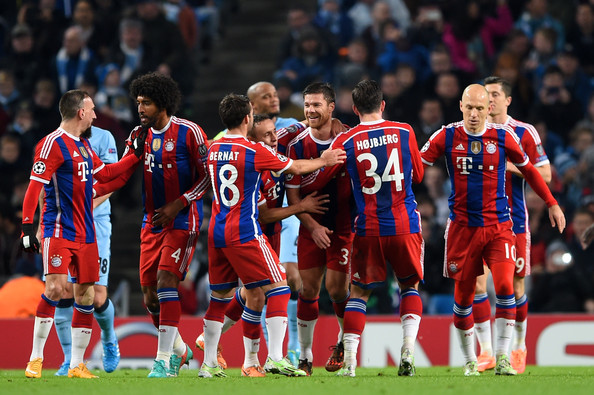 Xabi Alonso (C) #3 of Bayern Muenchen is congratulated by teammates after scoring a goal to level the scores at 1-1 during the UEFA Champions League Group E match between Manchester City and FC Bayern Muenchen at the Ethad Stadium on November 25, 2014 in Manchester, United Kingdom.