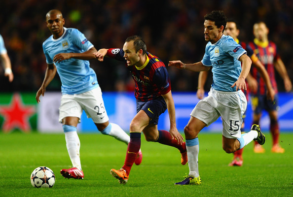 Andres Iniesta of Barcelona competes with Jesus Navas of Manchester City during the UEFA Champions League Round of 16 first leg match between Manchester City and Barcelona at the Etihad Stadium on February 18, 2014 in Manchester, England.