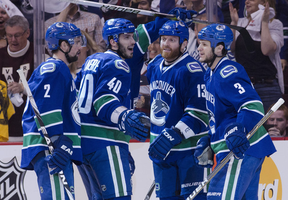 Raffi Torres #13 (middle) of the Vancouver Canucks is congratulated by Dan Hamhuis #2, Maxim Lapierre #40 and Kevin Bieksa #3 of the Vancouver Canucks after scoring against the Nashville Predators during the first period in Game Five of the Western Conference Semifinals during the 2011 NHL Stanley Cup Playoffs on May 07, 2011 at Rogers Arena in Vancouver, British Columbia, Canada.