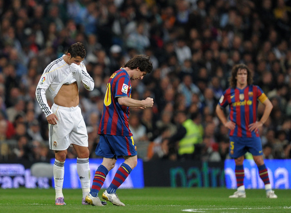 Cristiano Ronaldo Lionel Messi (R) of FC Barcelona clenches his fists celebrating scoring his sides opening goal backdropped by Cristiano Ronaldo of Real Madrid during the La Liga match between Real Madrid and Barcelona at the Estadio Santiago Bernabeu on April 10, 2010 in Madrid, Spain.