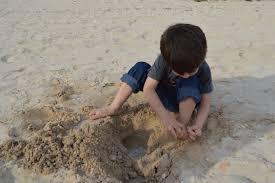 niño jugando con la arena de la playa