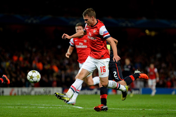 Aaron Ramsey Aaron Ramsey of Arsenal chips the ball into the net to score his team's third goal during the UEFA Champions League Group B match between Arsenal FC and Olympiacos FC at Emirates Stadium on October 03, 2012 in London, England.