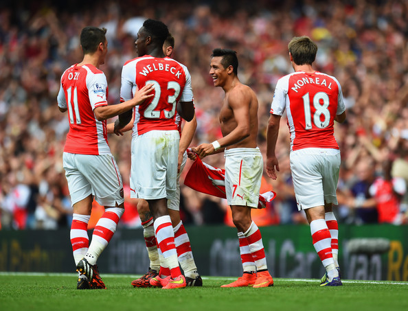 Alexis Sanchez of Arsenal celebrates scoring their second goal with team mates during the Barclays Premier League match between Arsenal and Manchester City at Emirates Stadium on September 13, 2014 in London, England.