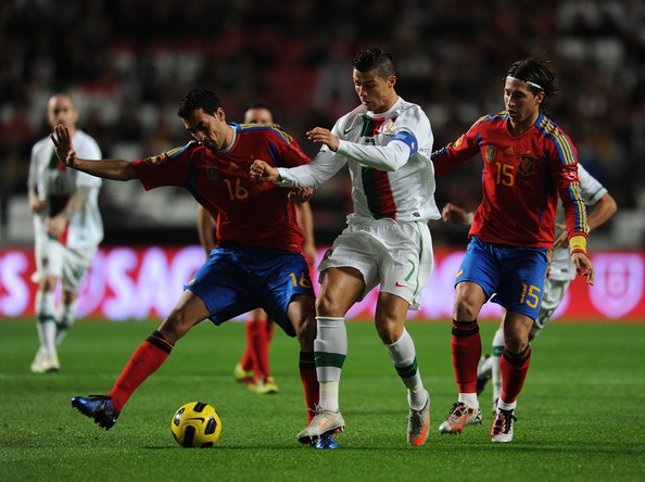 Cristiano Ronaldo (C) of Portugal duels for the ball with Sergio Busquets (L) and Sergio Ramos of Spain during the International Friendly match between Portugal and Spain at the Estadio da Luz on November 17, 2010 in Lisbon, Portugal. Spain lost the match 4-0.