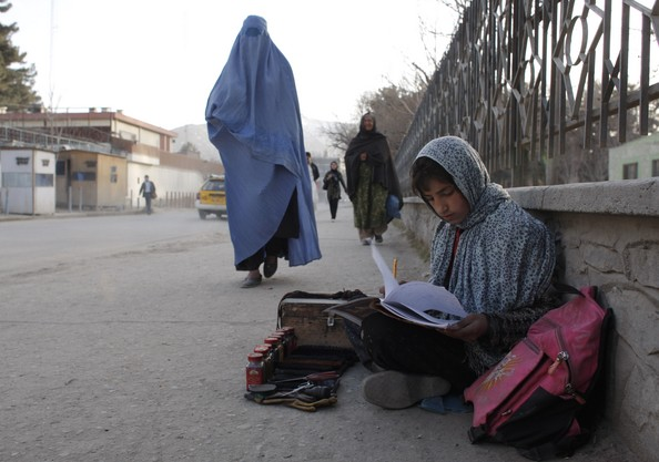 Anayetah,12, does her homework while waiting for customers to polish shoes after attending classes at the Aschiana school February 28, 2008 in Kabul, Afghanistan. Aschiana schools assist thousands of children whose parents cannot afford to send them to regular public schools. There are currently eight Aschiana schools located around Kabul attending to approximately 10,000 needy students, the majority of them are girls ranging from ages seven to 17. Coming from poor households most of the children are forced to work after school, cleaning cars, polishing shoes, or collecting garbage. (February 27, 2008 - Photo by Paula Bronstein/Getty Images AsiaPac)