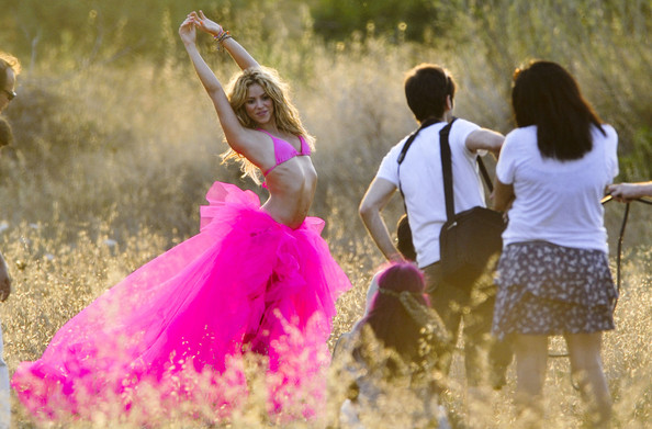 Shakira stands out in hot pink  for a photo shoot in a field. The singer shows off her flexibility by  stretching for some poses.