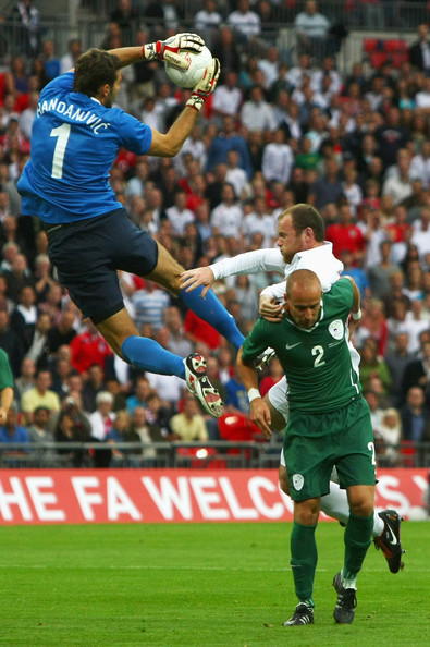 Wayne Rooney (C) of England challenges Miso Brecko (R) and Samir Handanovic (L) the Slovenia goalkeeper in the air during the International Friendly match between England and Slovenia at Wembley Stadium on September 5, 2009 in London, England.