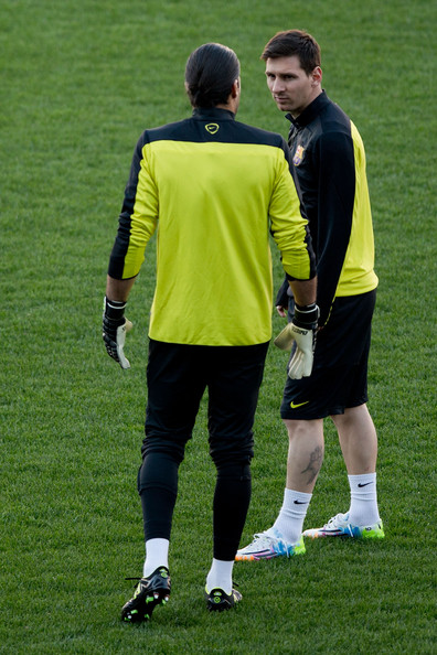 Lionel Messi (R) of FC Barcelona speaks with his teammate goalkeeper Jose Manuel Pinto (L) during the training session the day before the UEFA Champions League Quarter-final match between Atletico de Madrid and FC Barcelona at Vicente Calderon Stadium on April 8, 2014 in Madrid, Spain.
