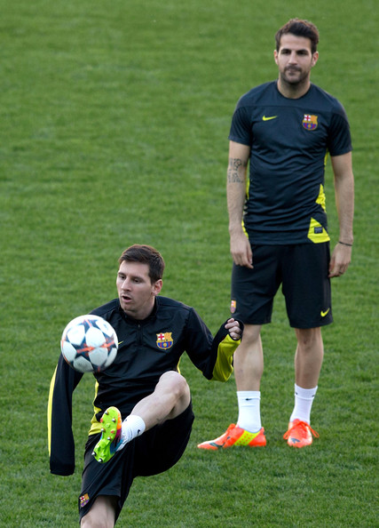 Lionel Messi (L) of FC Barcelona controls the ball as his teammate Cesc Fabregas (R) looks on during a training session the day before the UEFA Champions League Quarter-final match between Atletico de Madrid and FC Barcelona at Vicente Calderon Stadium on April 8, 2014 in Madrid, Spain.