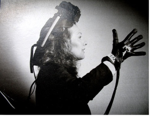The black and white image shows a women with a 1950s hairstyle wearing a head piece and black glove, connected by cables.