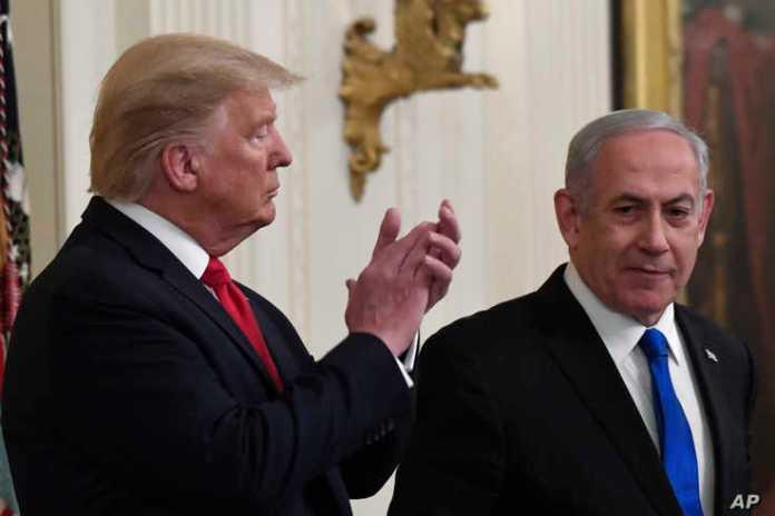 President Donald Trump, left, listens as Israeli Prime Minister Benjamin Netanyahu, right, speaks during an event in the East…