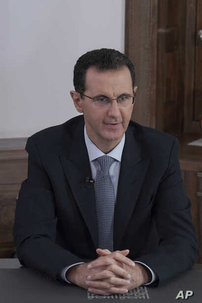 In this photo released on the official Facebook page of the Syrian Presidency, Syrian President Bashar Assad speaks during a…