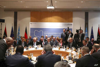 Members of the international committee take their seats for a follow-up meeting on Libya, arranged by German Foreign Minister Heiko Maas, in Munich, Germany, Feb. 16, 2020.