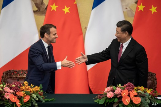 French President Emmanuel Macron, left, shakes hands with Chinese President Xi Jinping following a signing ceremony at the…
