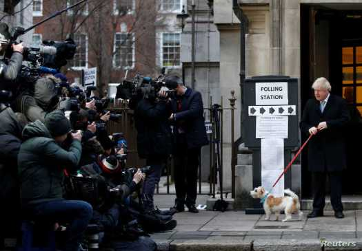 Britain's Prime Minister Boris Johnson arrives with his dog Dilyn at a polling station, at the Methodist Central Hall, to vote…