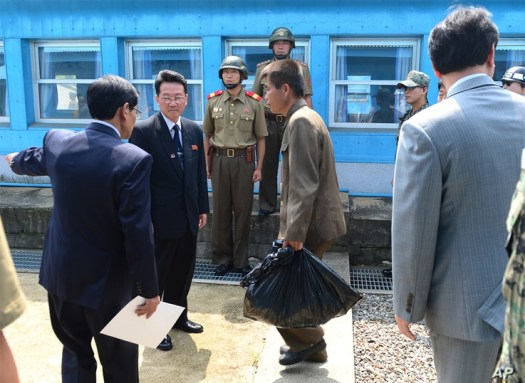 In this photo provided by the Unification Ministry, an unidentified North Korean fisherman, center, crosses the borderline at…