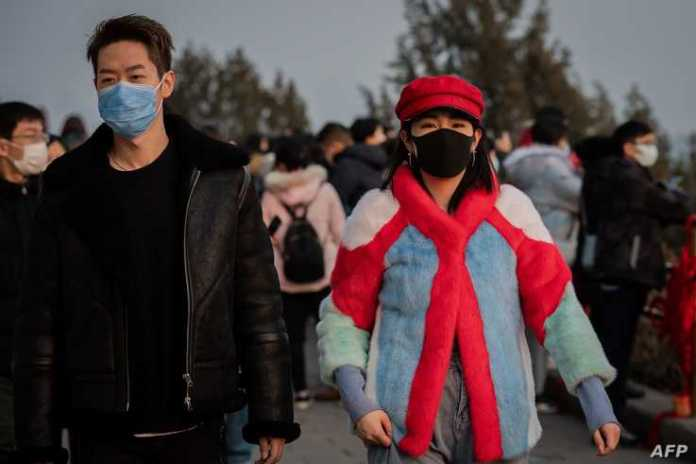 A couple wears protective facemasks to help stop the spread of a deadly SARS-like virus which originated in the central city of…
