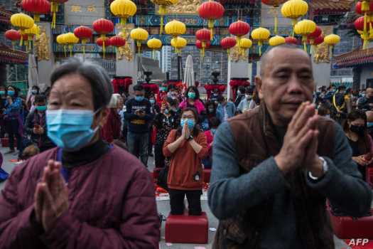 TOPSHOT - People wear masks as they pray at Wong Tai Sin temple on the first day of the Lunar New Year of the Rat in Hong Kong…