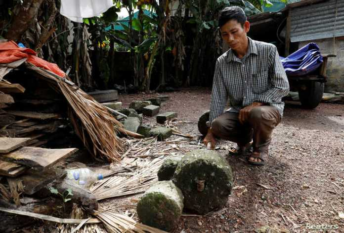 Nguyen Dinh Gia shows a barbell which was used by his son Nguyen Dinh Luong, a victim who was found dead in the back of British…