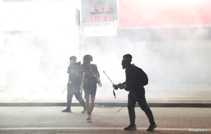 Anti-government protesters react as police fire tear gas during a demonstration, in Hong Kong, Nov. 2, 2019.