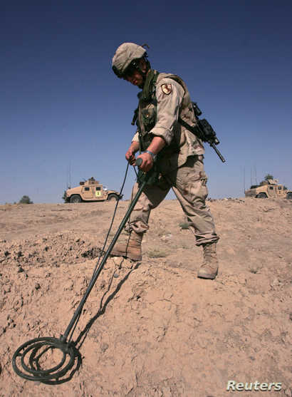 A U.S. Army soldier searches for explosive devices on the side of a road in Baghdad August 5, 2005. It's tedious work in…