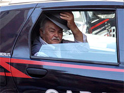 An unidentified man doffs his hat, as he rides in a Carabinieri (Paramilitary police) car after being arrested in Reggio Calabria, southern Italy, July 13, 2010, following one of the biggest operations ever against the powerful 'ndrangheta crime organization.